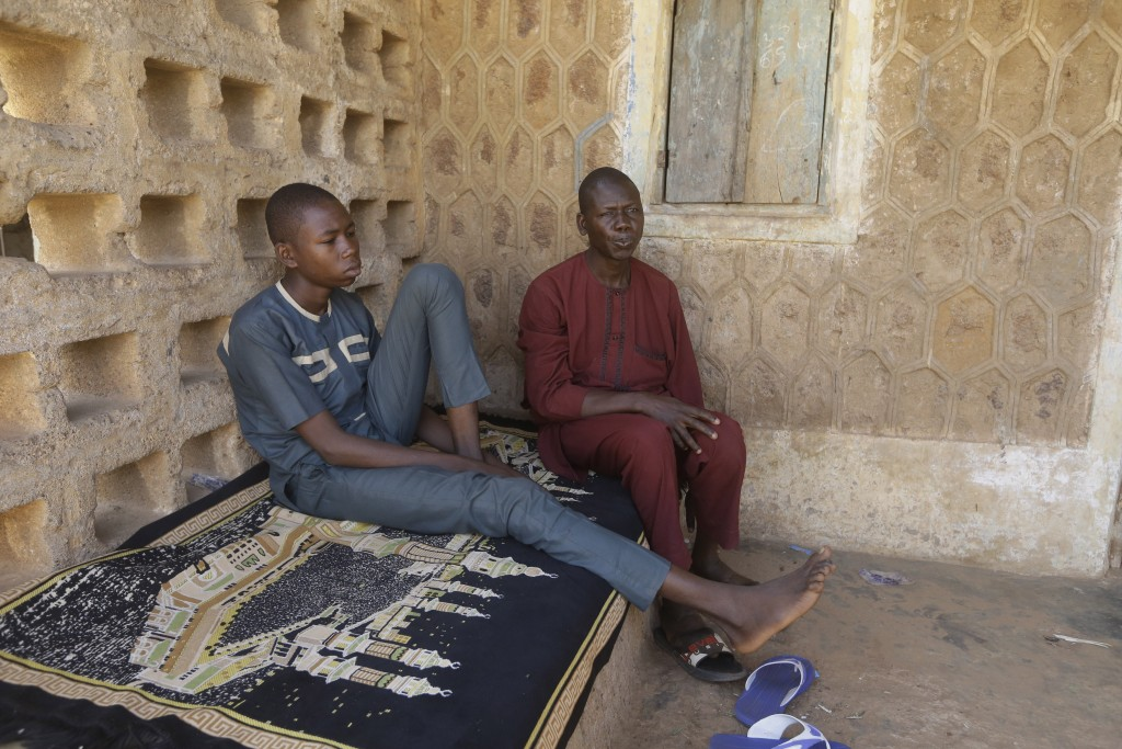 Usama Aminu, 17, a kidnapped student of Government Science Secondary School who escaped from bandits, left, and his father Aminu Male, sit together du...