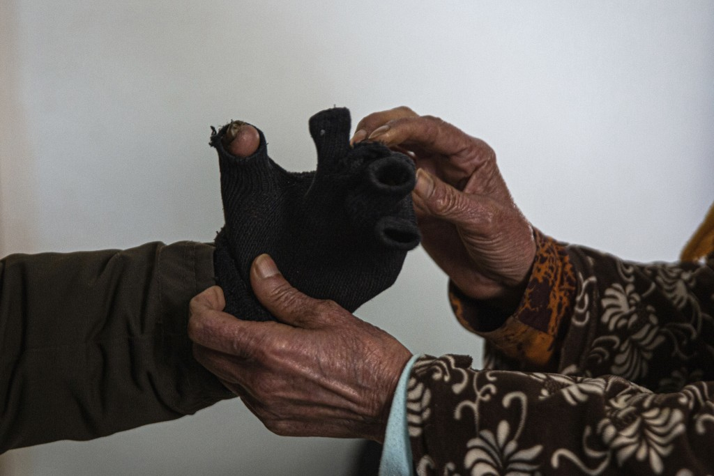 Zina Sehi, right, helps her son, Hosni Kalaia, to put on gloves in Kasserine, Tunisia, on Friday, Dec. 11, 2020. Kalaia is among hundreds of Tunisians...