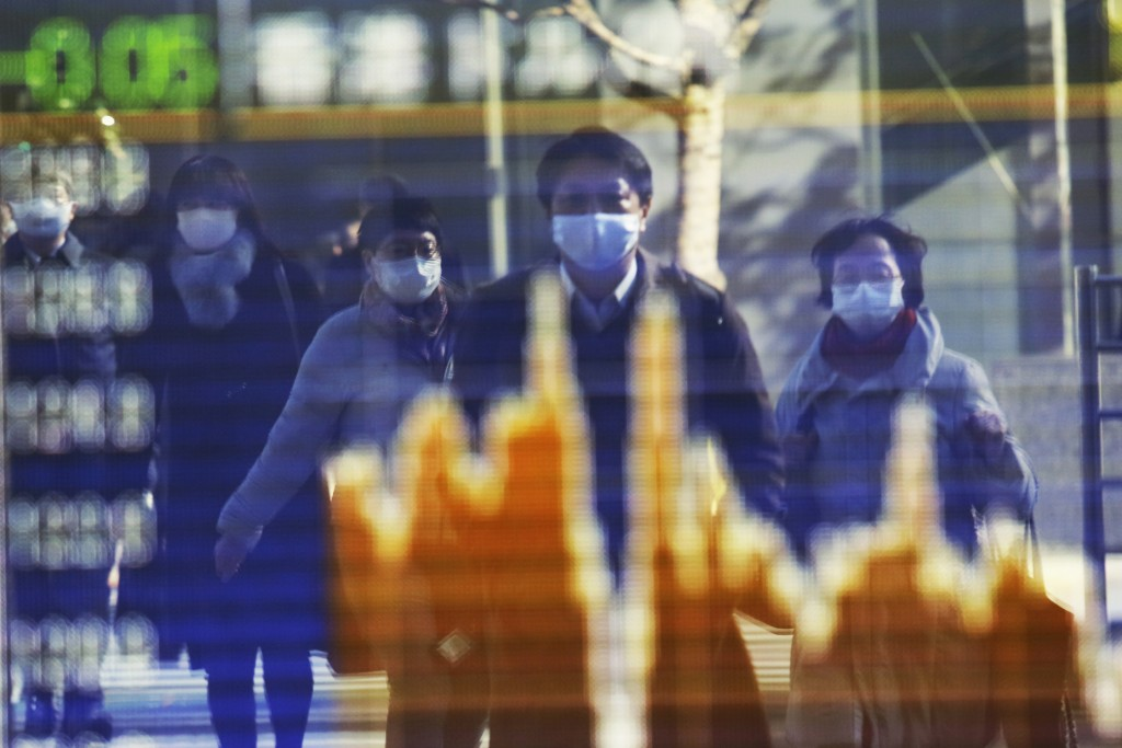 People wearing face masks to protect against the spread of the coronavirus reflected on the electronic board of a securities firm in Tokyo, Wednesday,...