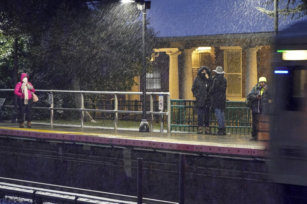 People wait for an arriving Long Island Rail Road train in the Queens borough of New York as snow starts to fall, Wednesday, Dec. 16, 2020. (AP Photo/...