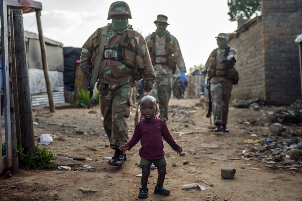 South African National Defense Forces patrol the Sjwetla informal settlement after pushing back residents into their homes, on the outskirts of the Al...