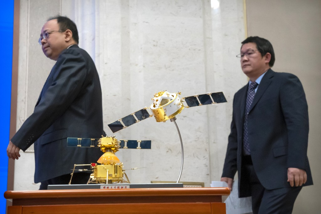 Officials walk past a model of China's Chang'e 5 lunar orbiter and lander during a press conference at the State Council Information Office in Beijing...