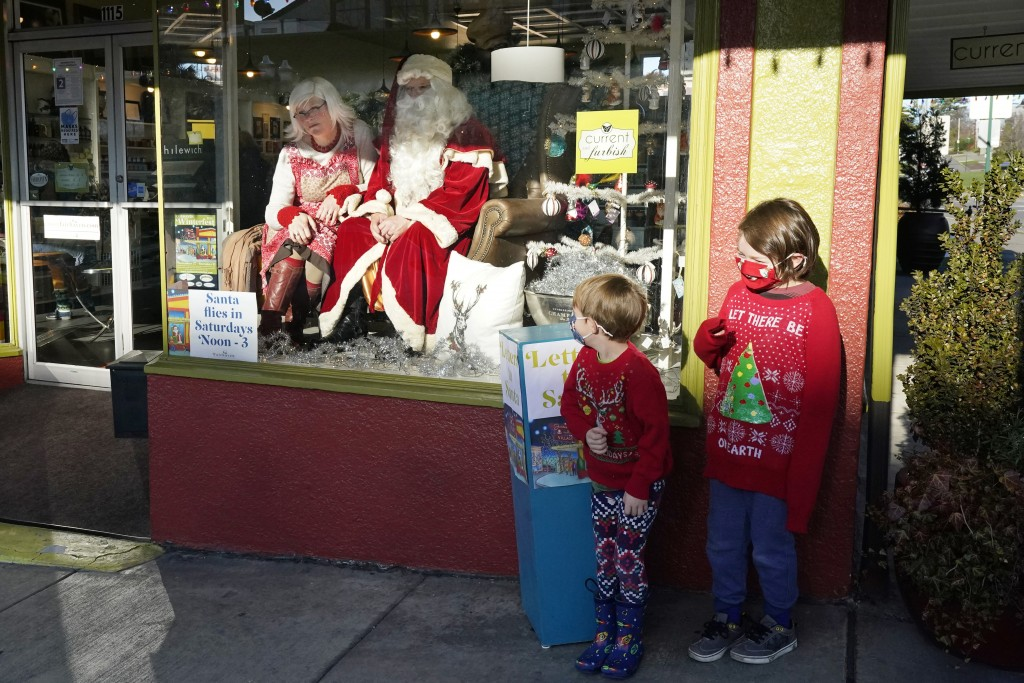 Beckett, right, and Hudson Gravley stand on the sidewalk in front of a storefront to pose for a photo with Santa and his wife, Mrs. Claus, in Bellingh...