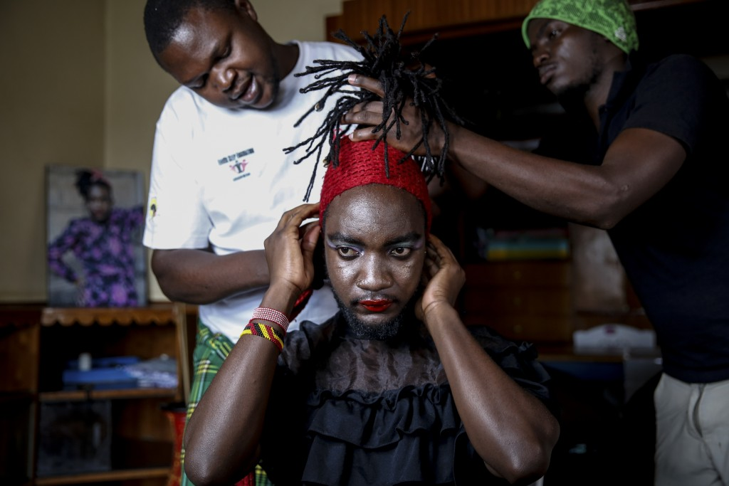 """Raymond Brian, center, a Ugandan refugee and a nonconforming gender person who also goes by the name of """"Mother Nature"""" has his make-up done by fellow..."""