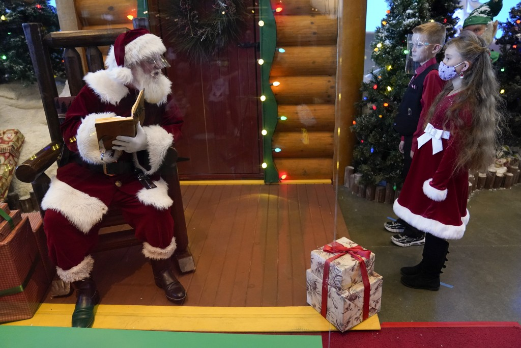 William Peargin, 8, and Payton Peargin, 8, right, stand six feet from Santa Claus, who sits behind a sheet of plexiglass, at Bass Pro Shop in Rancho C...