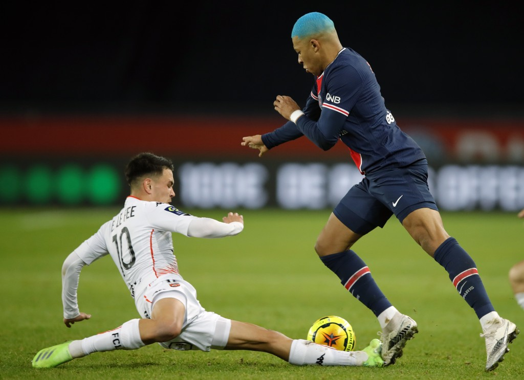 PSG's Kylian Mbappe, right, challenges with Lorient's Enzo Le Fee, during the French League One soccer match between Paris Saint-Germain and Lorient a...