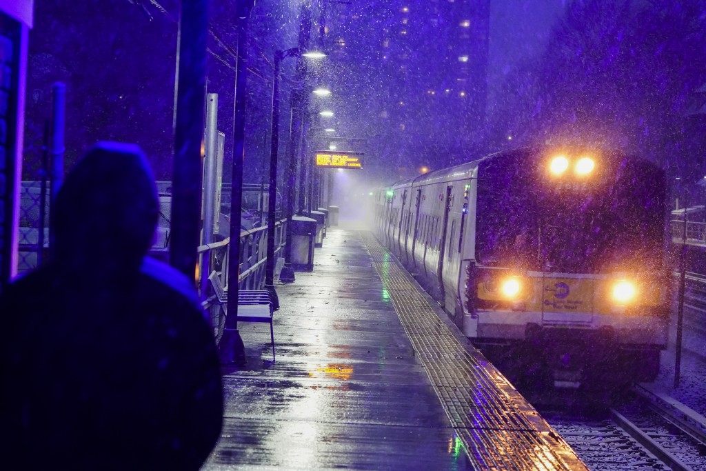 A woman waits for a Long Island Rail Road train in the Queens borough of New York as snow falls at the start of an oncoming snow storm, Wednesday, Dec...