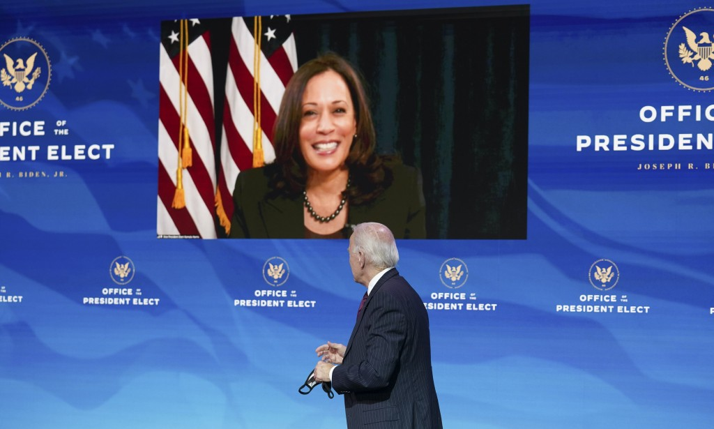 President-elect Joe Biden looks to Vice President-elect Kamala Harris as she attends a news conference via video at The Queen theater in Wilmington, D...