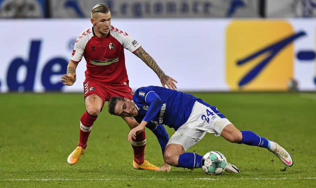 Freiburg's Jonathan Schmid, left, and Schalke's Bastian Oczipka challenge for the ball during the German Bundesliga soccer match between FC Schalke 04...