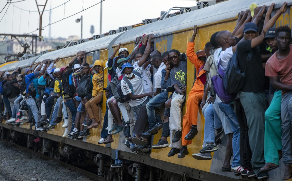 Train commuters hold on to the side of an overcrowded passenger train in Soweto, South Africa, Monday, March 16, 2020. (AP Photo/Themba Hadebe, File)