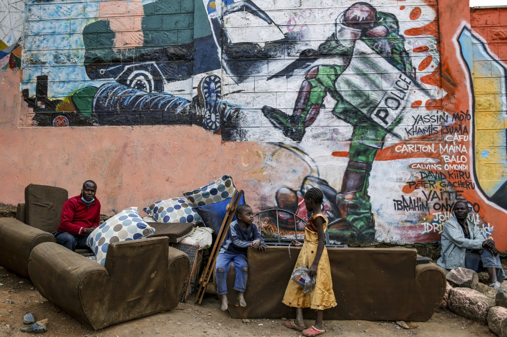 Kenyan children and men are photographed in front of a new mural painted this week showing an incident in 2016 when a Kenyan riot policeman repeatedly...