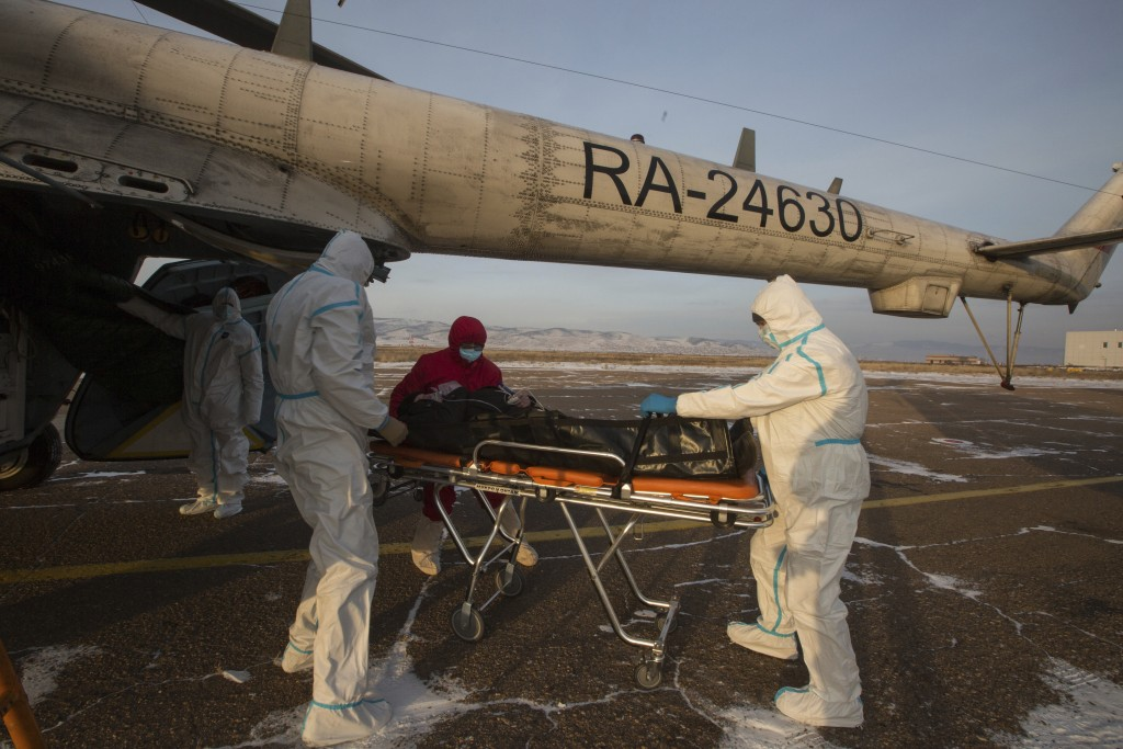 Medical workers transport a patient suspected of having coronavirus from an ambulance helicopter to a hospital outside Ulan-Ude, the capital of the Ru...