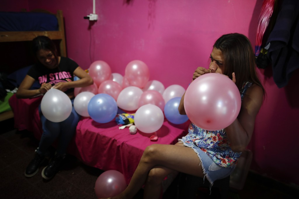Transgender woman Lourdes Figueroa inflates balloons at Hotel Gondolin, where she lives, to celebrate Pride Day in Buenos Aires, Argentina, Saturday, ...