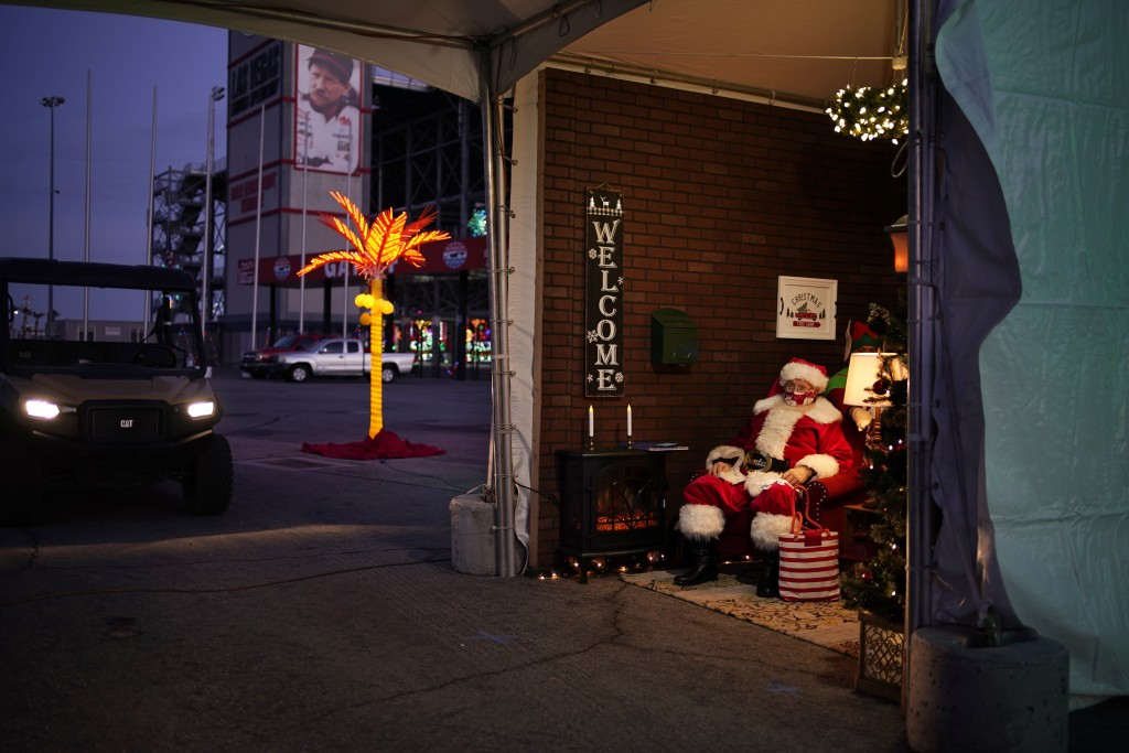 Bill Sandeen, dressed as Santa Claus, waits for cars at a drive-thru Santa selfie station at Glittering Lights, a drive-thru holiday lights display in...