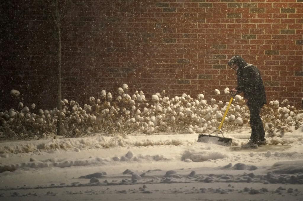A man shovels snow on the Villanova University campus during a winter storm, Wednesday, Dec. 16, 2020, in Villanova, Pa. (AP Photo/Matt Slocum)