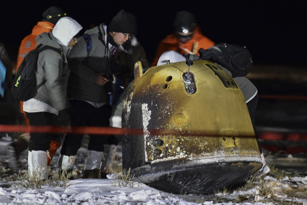 In this photo released by Xinhua News Agency, recovery crew members check on the capsule of the Chang'e 5 probe after its successful landed in Siziwan...