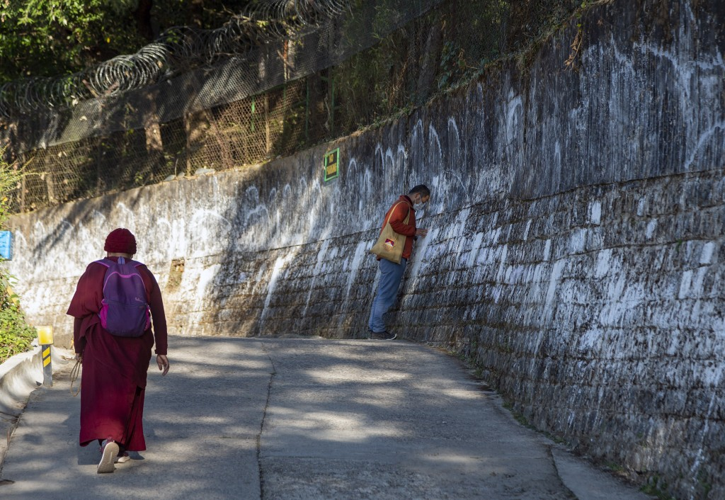 An exile Tibetan Buddhist nun walks past another Tibetan touching his head in reverence on the outer wall of the residence of Tibetan spiritual leader...