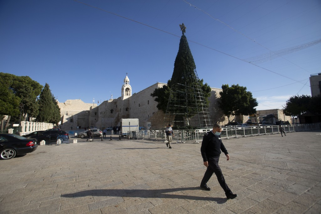 A man walks outside the Church of the Nativity, traditionally believed to be the birthplace of Jesus Christ, in the West Bank City of Bethlehem, Monda...