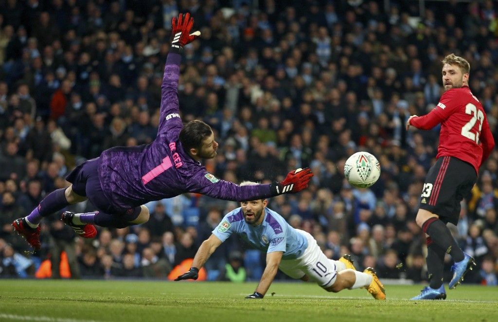 Manchester United's goalkeeper David de Gea dives for the ball in front of Manchester City's Sergio Aguero, center, and Manchester United's Luke Shaw,...