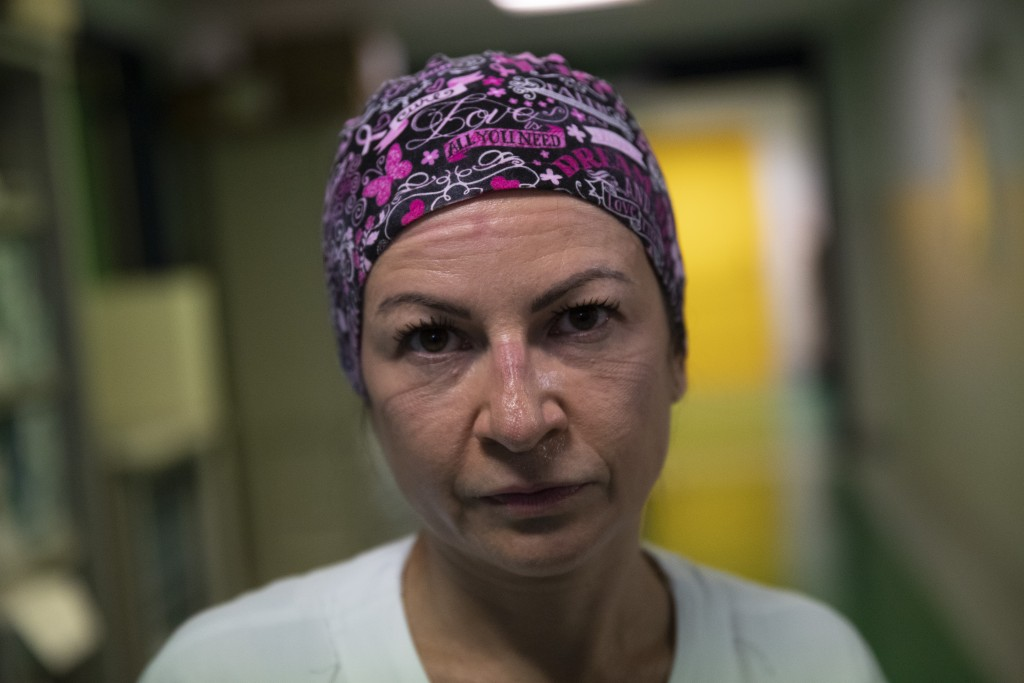 Nurse Glenda Grossi poses for a portrait at the end of her shift in the COVID-19 ICU of the Tor Vergata Polyclinic Hospital, Sunday, Dec. 13, 2020. Th...