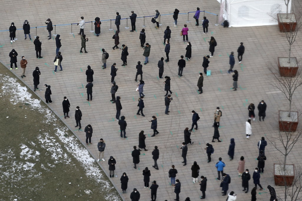 People queue in line to wait for coronavirus testing while maintaining social distancing at Seoul Plaza in Seoul, South Korea, Friday, Dec. 18, 2020. ...