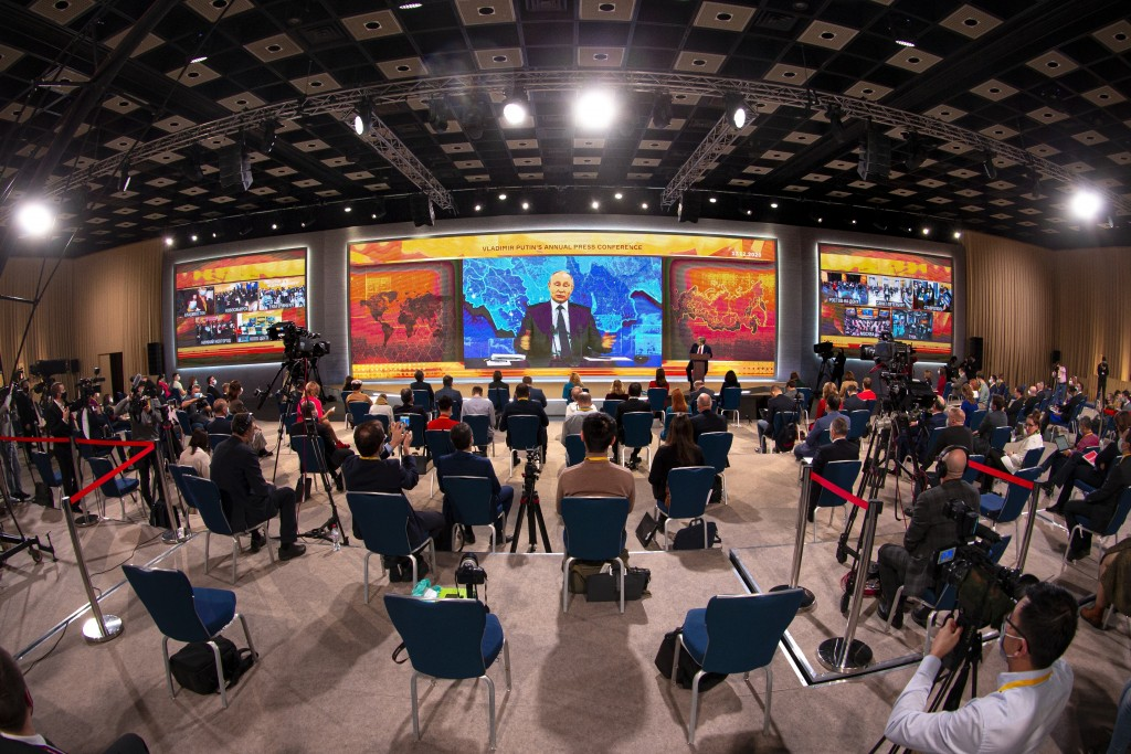 Russian President Vladimir Putin gestures as he speaks via video call during a news conference as journalists wearing face masks to protect against co...