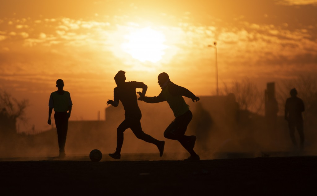 People play soccer in a dusty field in Soweto, South Africa, Wednesday, Aug. 19, 2020. South African president Cyril Ramaphosa announced that the enti...