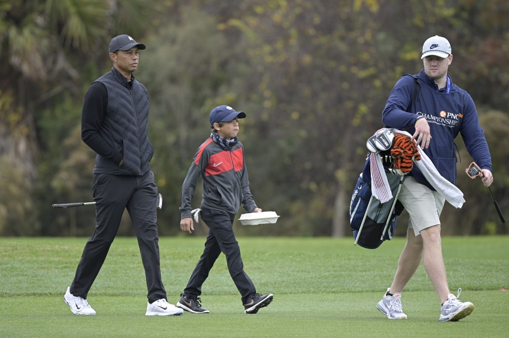 Tiger Woods, left, walks on the 11th fairway with his son Charlie during a practice round at the Father Son Challenge golf tournament, Thursday, Dec. ...