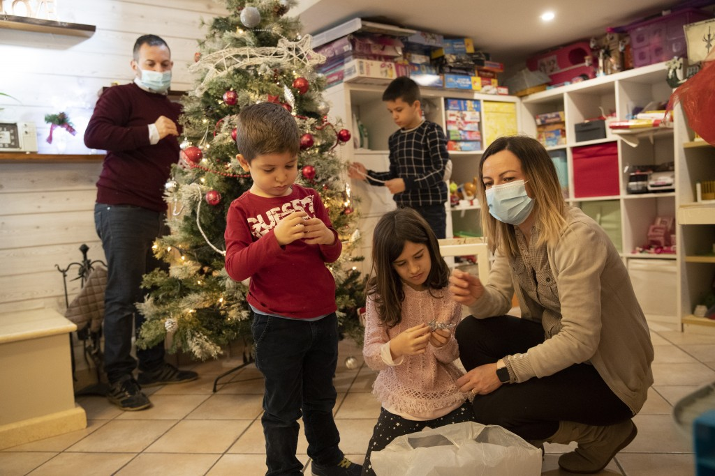Maurizio Di Giacobbe, left, and Glenda Grossi, right, place decorations on a Christmas tree, with their children from left, Tiziano, 4, Arianna, 9, an...
