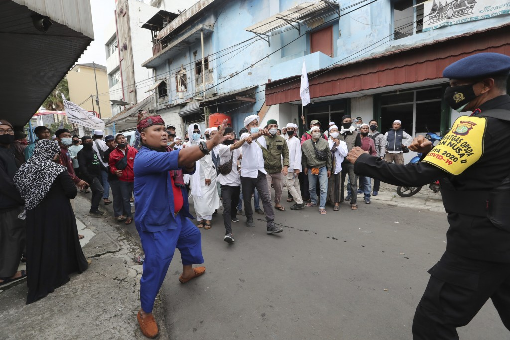 Supporters of Rizieq Shihab, leader of the Islam Defenders Front, confront a police officers during a rally in Jakarta, Indonesia, Friday, Dec. 18, 20...