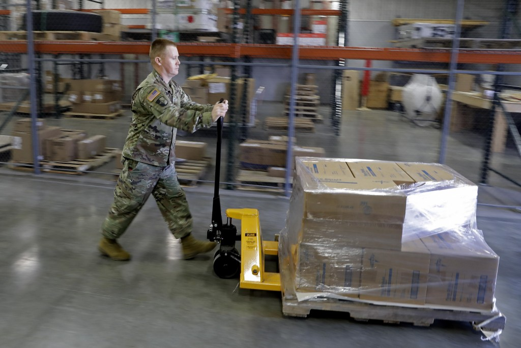 ADVANCE FOR RELEASE SATURDAY, DEC. 19, 2020 AND THEREAFTER -  FILE - In this March 26, 2020, file photo, an Indiana National Guardsman pushes a pallet...