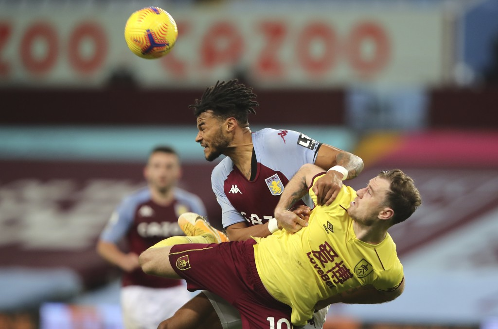 Aston Villa's Tyrone Mings, left, and Burnley's Ashley Barnes challenge for the ball during the English Premier League soccer match between Aston Vill...