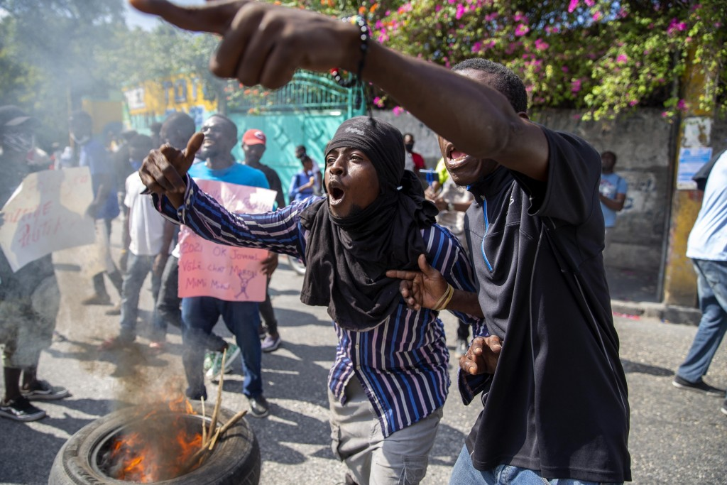 Protesters chant anti-government slogans during a protest demanding the release of political prisoners and the resignation of Haitian President Jovene...