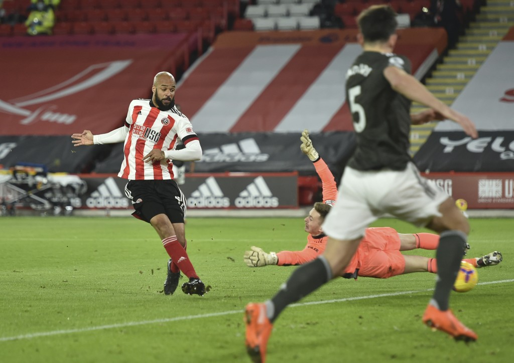 Sheffield United's David McGoldrick, left, shoots to score during the English Premier League soccer match between Sheffield United and Manchester Unit...