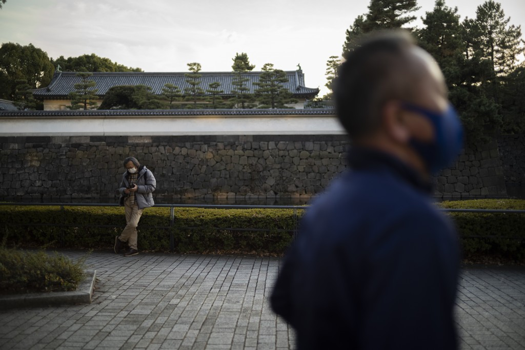 A man wearing a face mask to help curb the spread of the coronavirus rests by the East Gardens of the Imperial Palace as another man runs around the p...