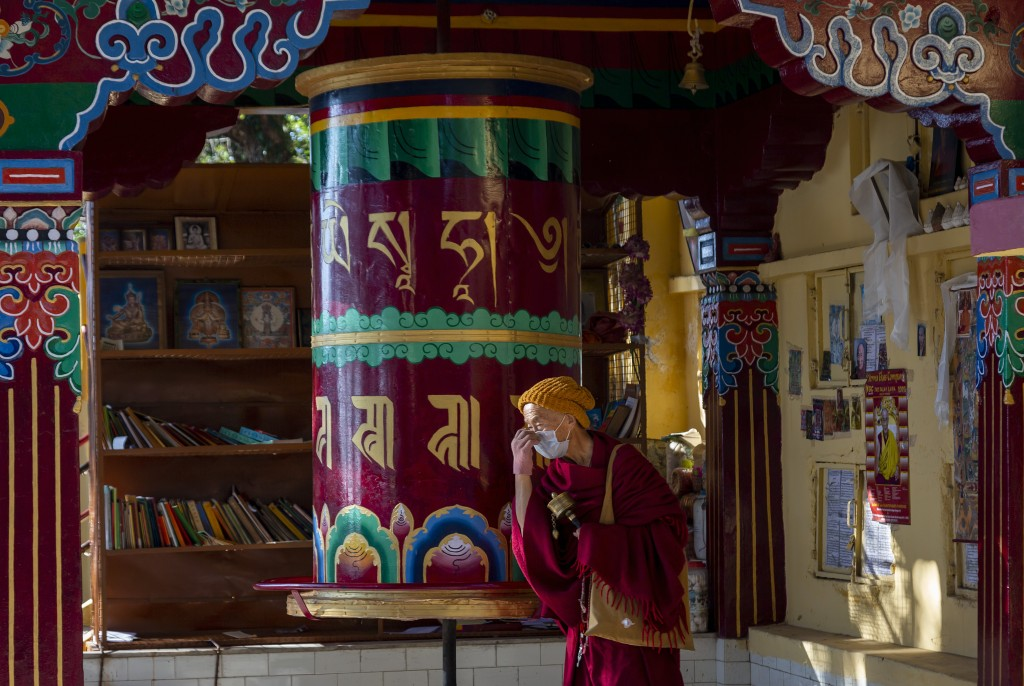 An exile Tibetan Buddhist monk wearing a mask as precaution against the coronavirus rotates a prayer wheel in Dharmsala, India, Friday, Dec. 18, 2020....