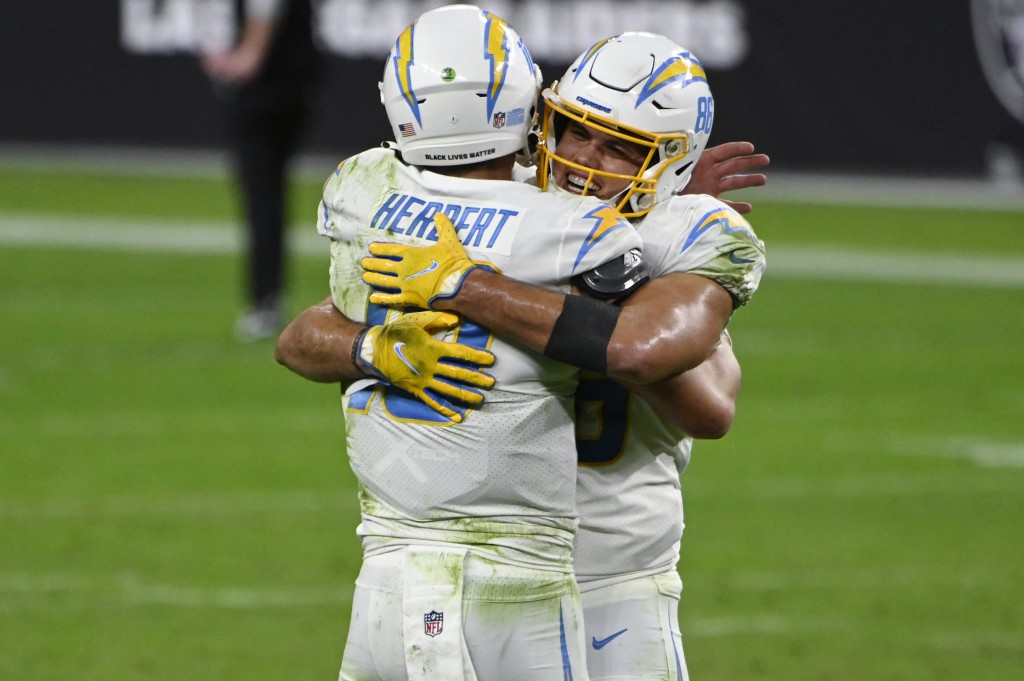 Los Angeles Chargers tight end Hunter Henry, right, embraces quarterback Justin Herbert (10) after defeating the Las Vegas Raiders in overtime of an N...