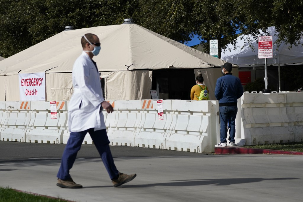 A medical worker passes a medical tent outside the emergency room at UCI Medical Center, Thursday, Dec 17, 2020, in Irvine, Calif. California health a...