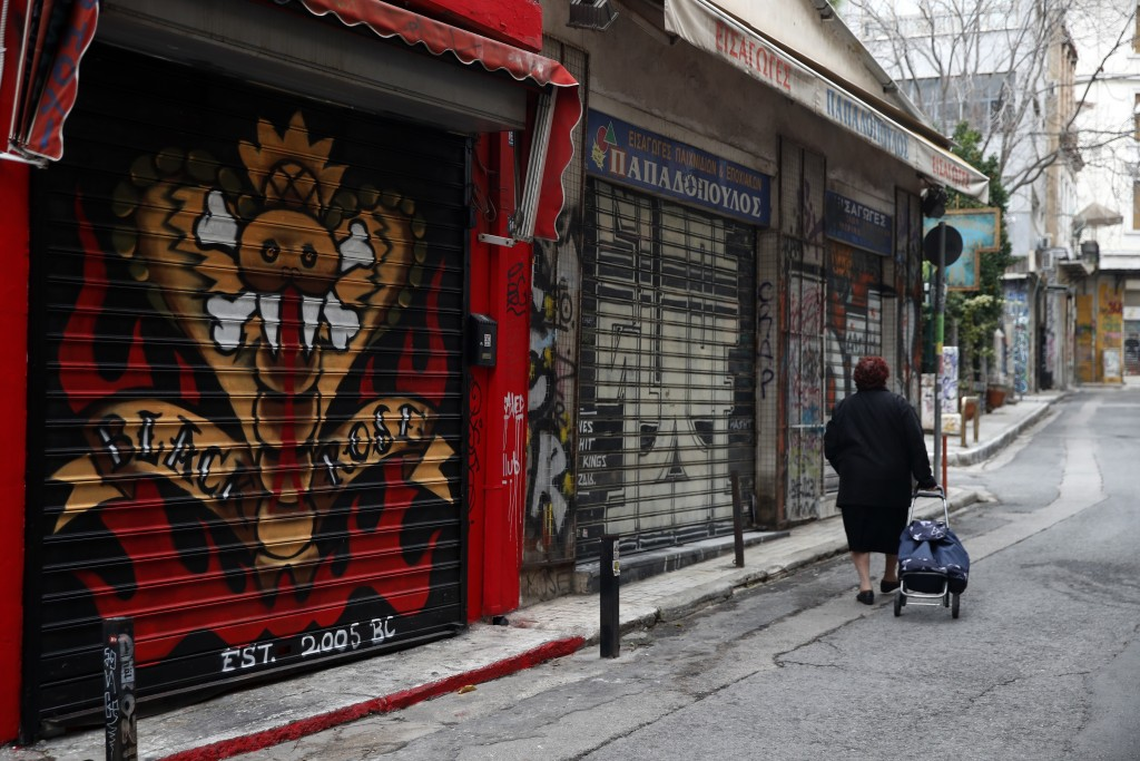 A woman pulls her shopping trolley in Athens, Friday, Dec. 18, 2020. Despite six weeks of lockdown measures, coronavirus deaths and infections remain ...