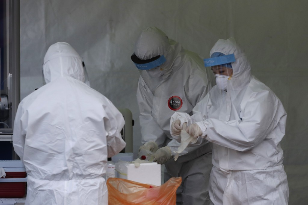 Medical workers wearing protective gear prepare to take sample during a COVID-19 test at a coronavirus testing site in Seoul, South Korea, Friday, Dec...