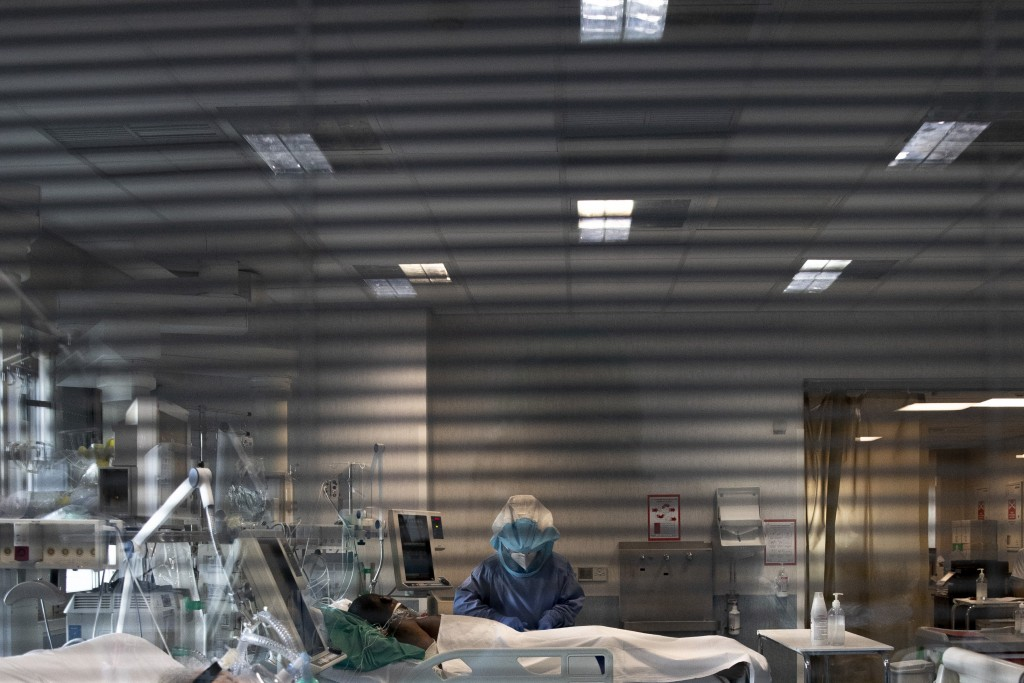 Nurse Maurizio di Giacobbe tends to a patient in the COVID-19 ICU of the Tor Vergata Polyclinic Hospital, Sunday, Dec. 13, 2020. The coronavirus pande...