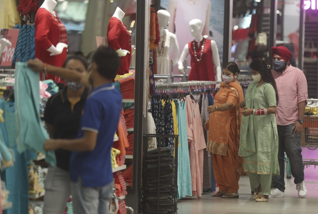 People wearing face masks shop in a mall in Mumbai, India, Friday, Dec. 18, 2020. (AP Photo/Rafiq Maqbool)
