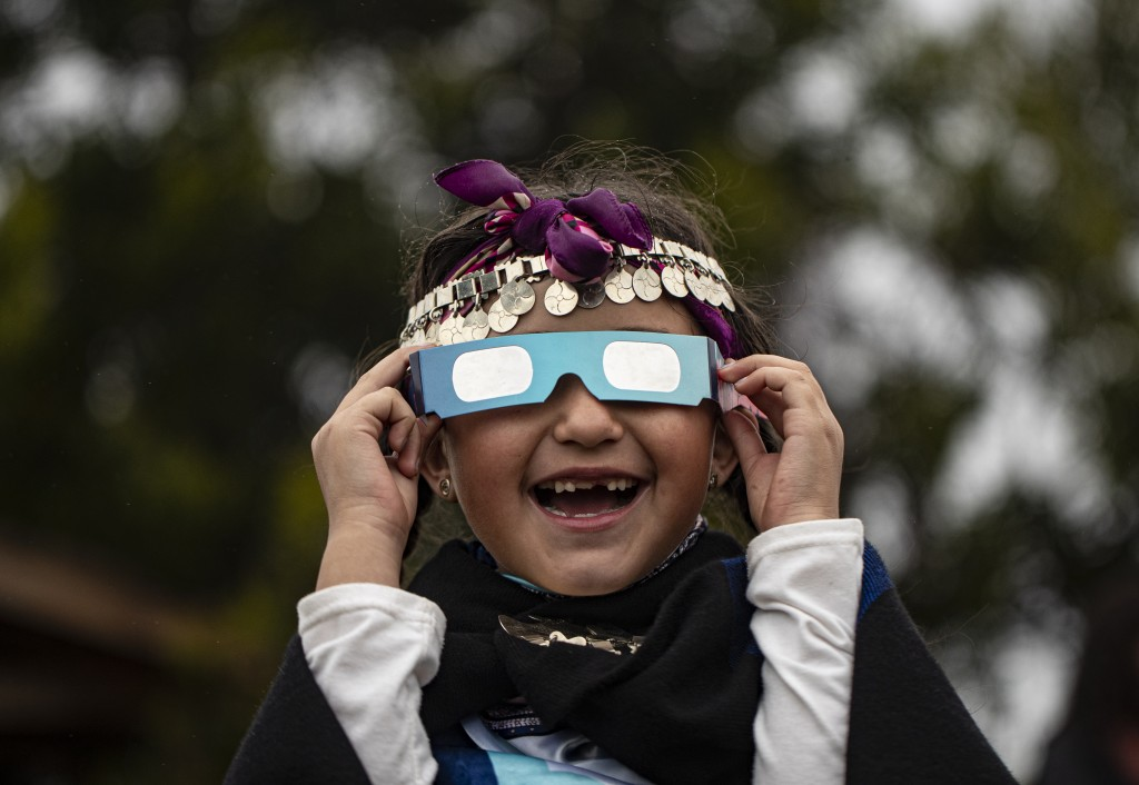 Magdalena Nahuelpan, a Mapuche Indigenous girl, looks at a total solar eclipse using special glasses in Carahue, La Araucania, Chile, Monday, Dec. 14,...