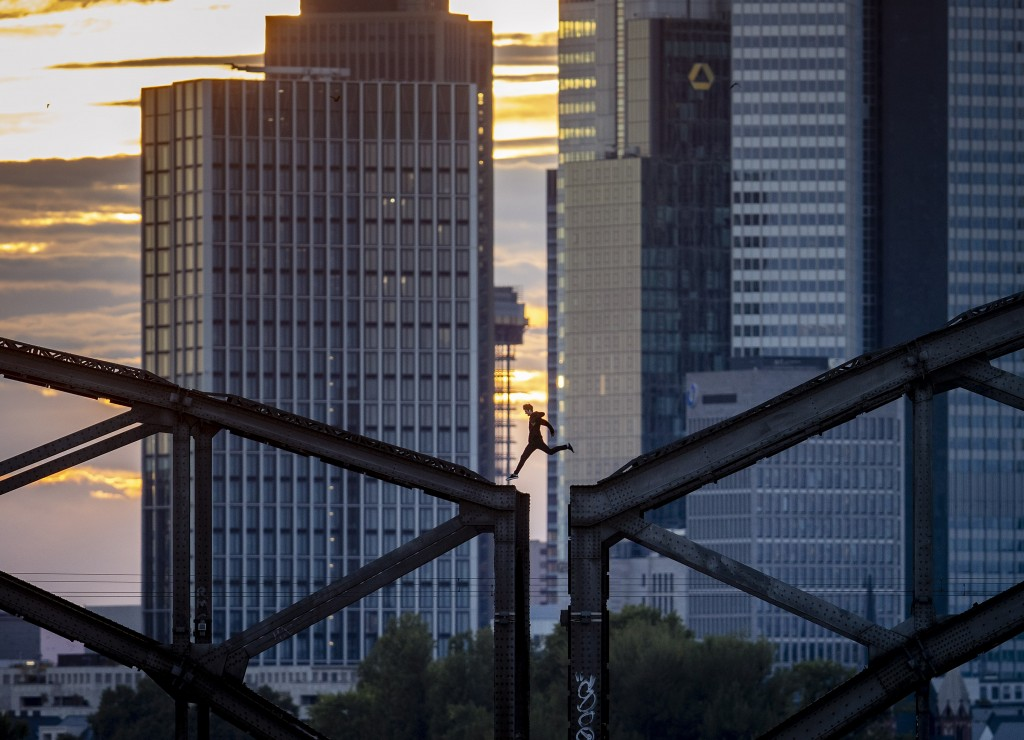A parkour runner jumps on a railway bridge with the buildings of the banking district in background in Frankfurt, Germany, Wednesday, Sept. 9, 2020. (...