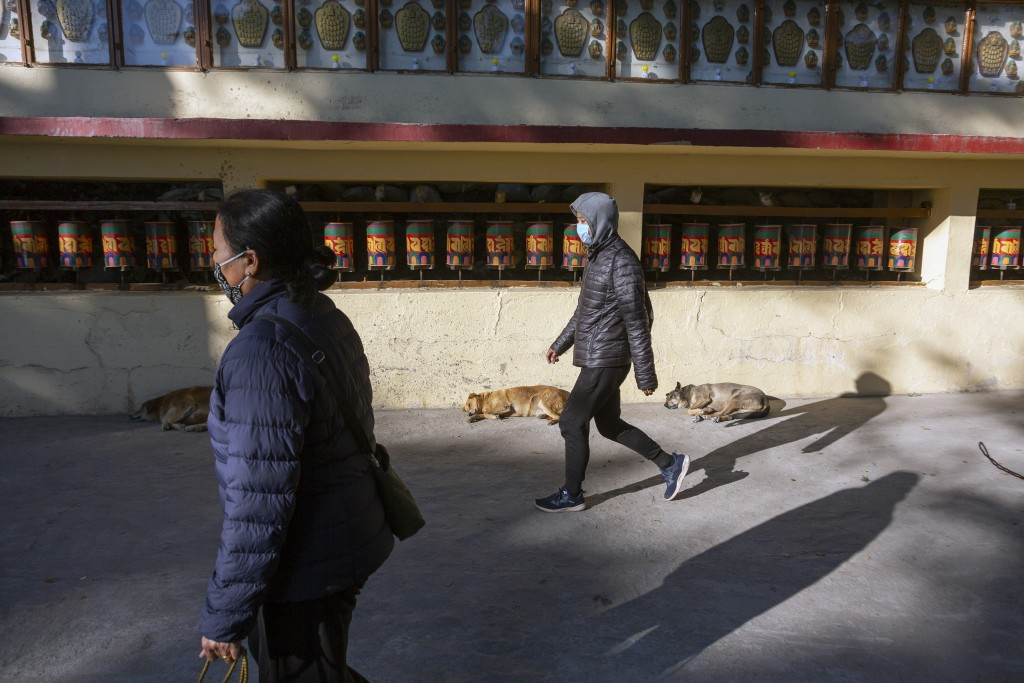 Exile Tibetans wearing masks as a precaution against the coronavirus walk past a row of Tibetan prayer wheels in Dharmsala, India, Friday, Dec. 18, 20...
