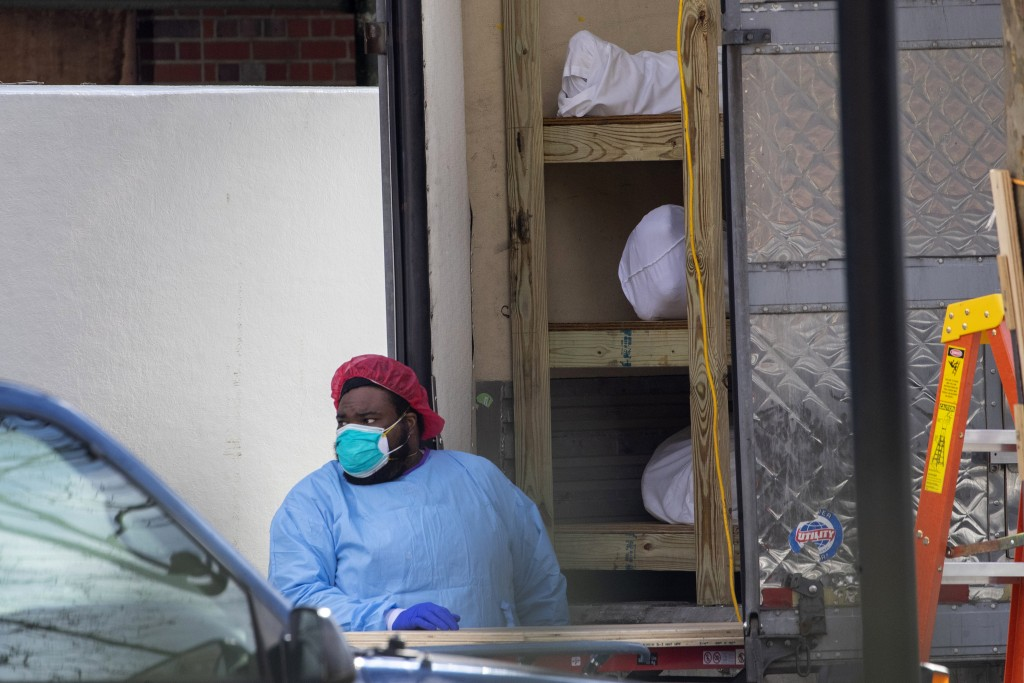 Medical personnel prepare to transport a body from a refrigerated container at Kingsbrook Jewish Medical Center, Wednesday, April 8, 2020, in the Broo...