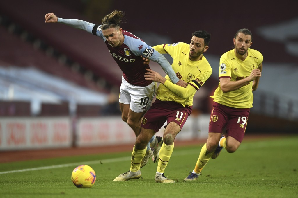 Aston Villa's Jack Grealish, left, and Burnley's Dwight McNeil challenge for the ball during the English Premier League soccer match between Aston Vil...
