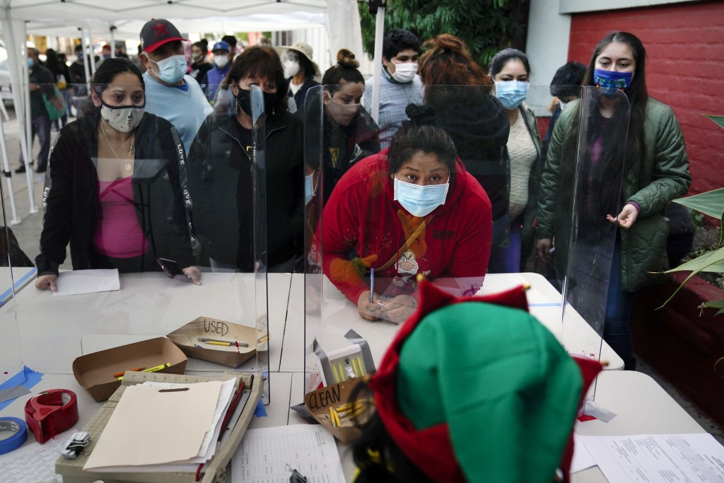 """People check in at a food bank held at Los Angeles Boys & Girls Club in the Lincoln Heights neighborhood of Los Angeles, Thursday, Dec. 17, 2020. """"Thi..."""