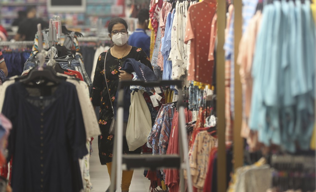 A woman wearing a face mask shops in a mall in Mumbai, India, Friday, Dec. 18, 2020. (AP Photo/Rafiq Maqbool)