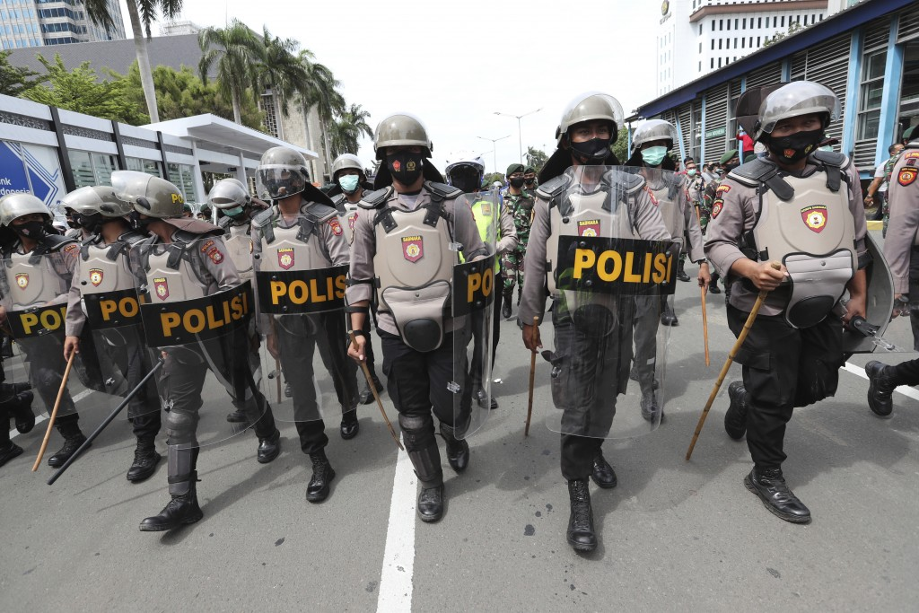Police officers in riot gear move to push back supporters of Rizieq Shihab, leader of the Islam Defenders Front, during a rally in Jakarta, Indonesia,...